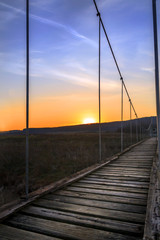 A wooden rope bridge at sunset