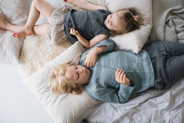 geschwister liegen zuhause in ihrem Kinderzimmer nebeneinander