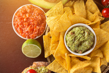 Tradition mexican guacamole and salsa dip, nachos tortilla chips.