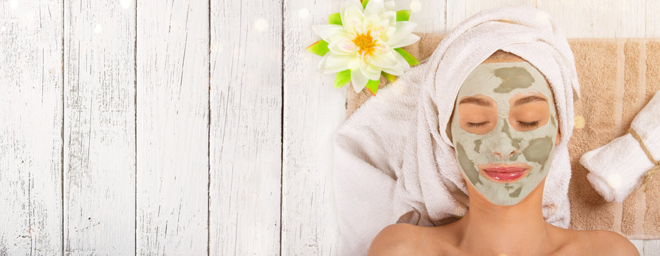 Young healthy woman with face clay mask.