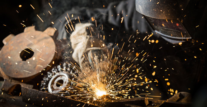 Welder working at the factory made metal