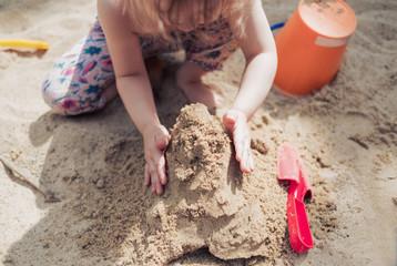 Kleines Mädchen spielt im Sand und baut eine Sandburg