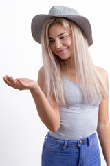 Cute trendy young blond woman in hat with a beaming happy smile looking at her empty hand extended to the side with copy space for your product placement isolated on white