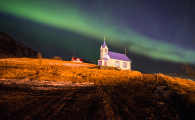The beautiful Aurora Borealis over the church in Stodvarfjordur town in East Iceland.