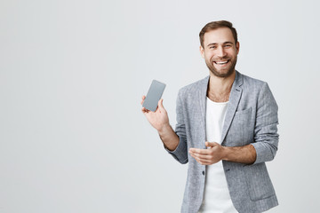 European bearded man in stylish jacket posing against gray background having happy expression while reading messages from friends, demonstrating screen of mobile phone. People and technology