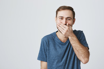Positive human expressions concept. Bearded caucasian male in blue t-shirt laughs at good joke, hides his smile behind his hand. Laughing man posing against gray studio wall.