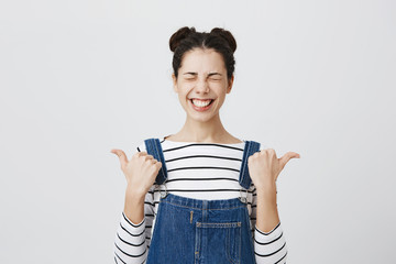 Positive funny brunette girl with hairbuns in striped top, clenching teeth in smile, closing eyes in joy points at copy space, poses at studio. Look at this wonderful thing! Advertising concept