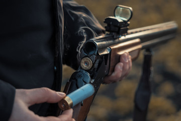 Sports shooting. Hunter reloading cartridge in field. Smoke from the trunks of smooth-bore hunting rifle after firing.