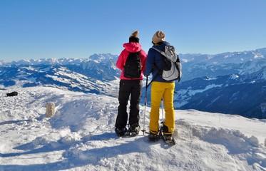 Zwei Frauen tragen Schneeschuhe im Schnee auf dem Berg Rigi / Schneeschuh Tour. Im Hintergrund verschneite Schweizer Berge