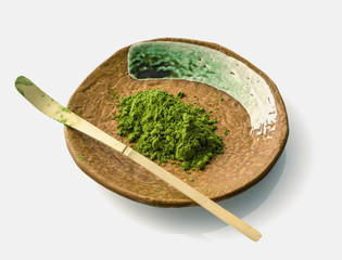 Japanese matcha green tea powder on a ceramic clay plate with a chasaku bamboo spoon (used to scoop the maccha in a bowl during tea ceremony) on white background.