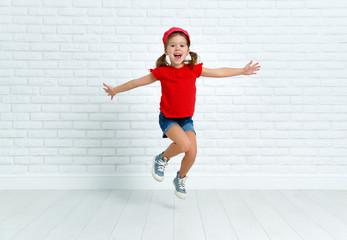 happy child girl jumping around empty wall