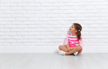 happy child girl near an empty brick wall