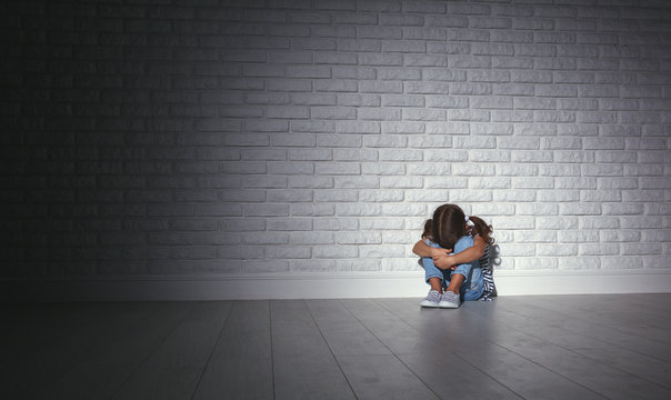 upset sad sad child girl in stress cries at an empty dark wall