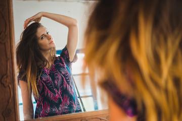 Woman adjusting hair at mirror