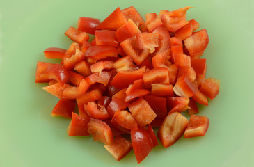 Chopped raw red bell pepper set out on light green plate as ingredient for cooking and meal preparation
