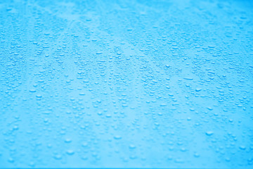 Water drops on a car glass in rainy day. Selective focus.
