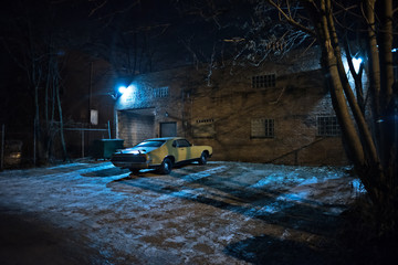 Wall Mural - Vintage muscle car in a dark Chicago city urban alley on a winter night.