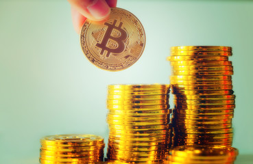 Hand hold a single bitcoin over Stack of gold bitcoins, Cryptocurrency concept. Virtual currency digital payment system