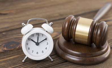 Alarm clock, judge hammer against the background of a wooden table. Time of the meeting. Justice.