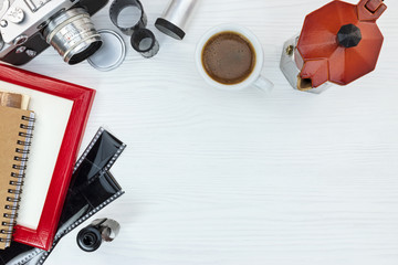 old camera, empty photo frame, negative films and red coffee pot with cup on white background, flat view