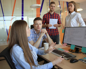 Group of young modern people in smart casual wear having a brainstorm meeting while standing in the creative office.