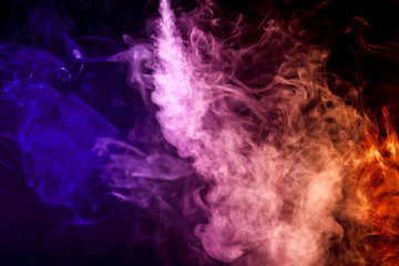 Thick colorful smoke of purple, lilac, orange  colors on a black isolated background. Background from the smoke of vape