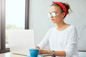 Serious female graphic designer works remotely on new project uses notebook, searches good ideas for project in internet, drinks tasty coffee. Woman sends messages or answers on laptop computer