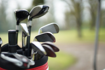 set of golf clubs in a golf bag with  fairway background