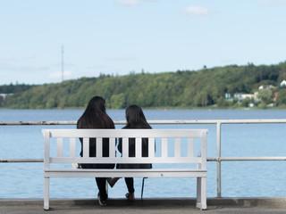 Two girls sitting on a beach in Viborg, Denmark