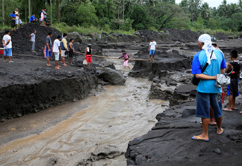 Residents watch a woman using an improvised bridge to avoid crossing a river with lahar flow coming from Mount Mayon volcano in Daraga, Albay province, south of Manila