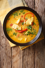 Brazilian food: Moqueca Baiana of fish and bell peppers in spicy coconut sauce close-up on a plate. Vertical top view
