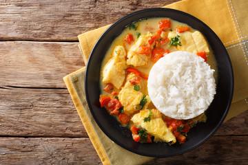 Pescado encocado or fish with coconut sauce is an Ecuadorian coastal dish close-up on a plate. horizontal top view