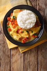 Pescado encocado or fish with coconut sauce is an Ecuadorian coastal dish close-up on a plate. Vertical top view