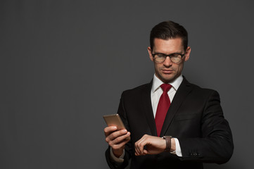 Portrait of successful young man hurrying on meeting  and looking at his watch with  smartphone in his hand on gray background. Copyspace