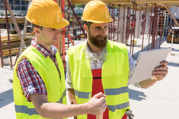 Two young workers watching a video with useful information or communicating online through a tablet PC during break on the construction site