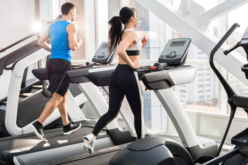 Back view of two fit young people, man and woman, running on treadmills facing windows in modern...