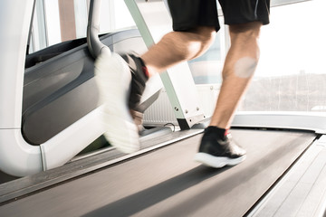 Blurred motion of muscular  male legs running on treadmill lit by sunlight
