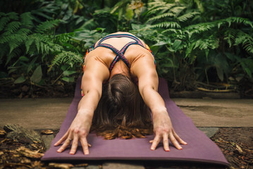Female yoga instructor stretching on a mat at botanical garden