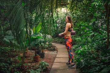 Positive female yoga instructor posing at greenhouse