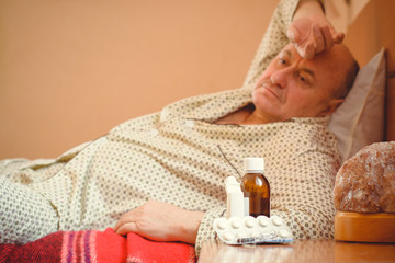 Worried senior lying in bed at home. Mature man lying in bed wear in pajamas, feeling pain, sick