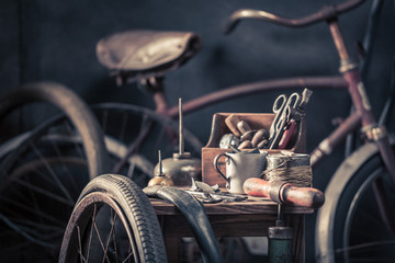 Old bicycle repair workshop with wheels, tools, and rubber patch