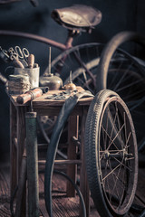 Vintage bicycle repair workshop with wheels, tools, and rubber patch
