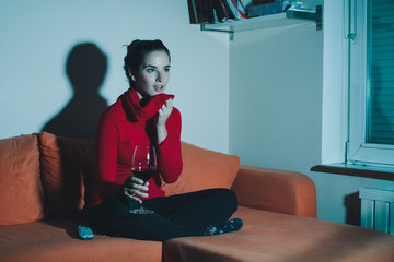 Young woman watching tv with glass of wine