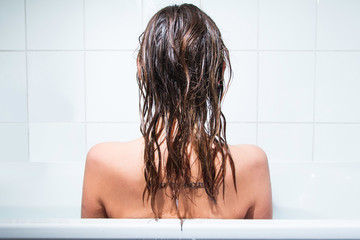 Young girl sitting in bathtub, alone and depressed, back, wet hair