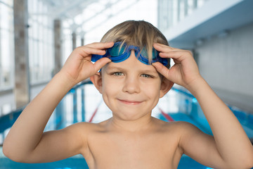 Head and shoulders portrait of cute little boy wearing watersport goggles looking at camera with wide smile while standing on edge of swimming pool