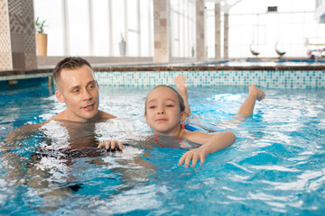 Portrait shot of handsome man teaching his frightened little daughter to swim in modern swimming pool with panoramic windows