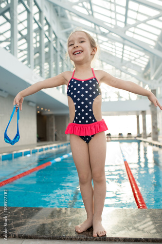 afb6773f14928 Full length portrait of happy little girl wearing swimsuit standing on edge  of swimming pool with outstretched arms and looking away with toothy smile