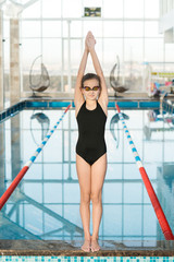 Full length portrait of smiling little swimmer wearing goggles standing on edge of swimming pool with raised hands and looking at camera