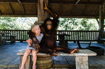 blond girl hugging a big monkey