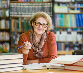 Portrait of an elderly woman with a book in the library